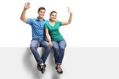 Ritratto integrale di giovane coppia casuale che si siede su un pannello e che ondeggia alla macchina fotografica fotografie stock libere da diritti