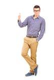 Ritratto integrale di un giovane che dà un pollice su Fotografia Stock