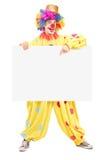 Ritratto integrale di un pagliaccio maschio felice che indica su un comitato Fotografia Stock