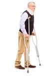 Ritratto integrale di un signore con il supporto del collo facendo uso di crutc Fotografia Stock Libera da Diritti