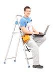 Ritratto integrale di un uomo pratico con un computer portatile che si siede su una l immagini stock