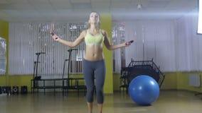 Ritratto integrale di una donna allegra che fa gli esercizi con la corda di salto isolata su un fondo bianco esaminando archivi video