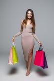 Ritratto integrale di una donna emozionante felice in sacchetti della spesa variopinti di condizione e della tenuta del vestito i Fotografia Stock