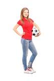 Ritratto integrale di una femmina sorridente dei giovani che tiene un calcio Immagini Stock Libere da Diritti