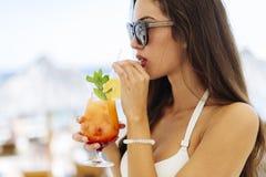 Ritratto laterale bevente del cocktail della donna attraente immagine stock libera da diritti