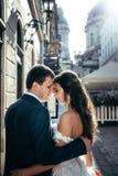 Ritratto laterale delle persone appena sposate sorridenti adorabili che abbracciano e che stanno morbidamente all'aperto testa a  Fotografia Stock Libera da Diritti