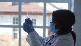 Ritratto laterale di giovane modello africano in occhiali e nella maschera medica che tengono la siringa con il vaccino sopra la  video d archivio