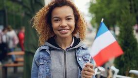 Ritratto lento della donna afroamericana graziosa e giovane che tiene la bandiera del francese e che sorride esaminando macchina  stock footage