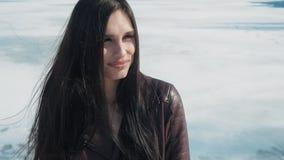 Ritratto lento di giovane bella donna castana nell'inverno su un fondo della neve del fiume congelato archivi video