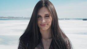 Ritratto lento di giovane bella donna castana nell'inverno su un fondo della neve del fiume congelato video d archivio