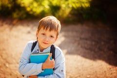 Ritratto Littleschoolboy con lo zaino ed i libri all'aperto Fotografie Stock Libere da Diritti