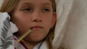 Ritratto malato del bambino con il termometro, ragazza malata a letto, bambino triste che soffre 4K freddo video d archivio