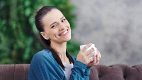 Ritratto medio del primo piano della donna domestica sorridente che tiene tazza bianca e che esamina macchina fotografica archivi video