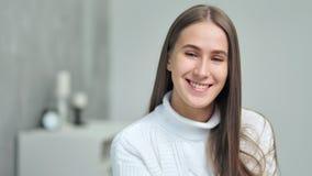 Ritratto medio del primo piano della giovane donna europea sorridente che esamina macchina fotografica video d archivio