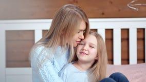 Ritratto medio del primo piano della giovane donna felice e piccola della figlia sveglia che abbracciano e che esaminano macchina archivi video