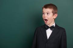 Ritratto molto emozionale del ragazzo di scuola vicino al fondo in bianco verde della lavagna, vestito in vestito nero classico,  Immagine Stock Libera da Diritti