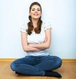 Ritratto naturale della donna Sedile sorridente della ragazza su un pavimento BAC bianco Immagini Stock