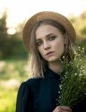 Ritratto naturale di una ragazza in un cappello di paglia con un mazzo di selvaggio immagine stock