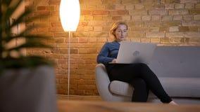 Ritratto nel profilo della donna caucasica senior che si siede sul sofà e che lavora con il computer portatile attentamente nella immagini stock libere da diritti