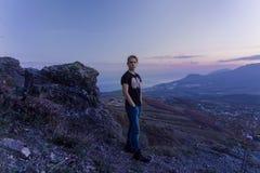 Ritratto nella crescita La giovane condizione attraente dell'uomo sulla cima delle montagne guarda alla macchina fotografica fotografia stock