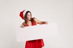 Ritratto orizzontale della ragazza di natale con il piatto su fondo bianco Immagini Stock