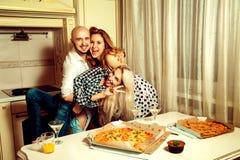 Ritratto orizzontale di divertimento tre genti ad un partito con pizza Immagini Stock
