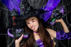 Ritratto orizzontale di una strega allegra con le scarpe in mani Immagine Stock