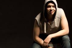 Ritratto oscuro di un giovane in una maglia con cappuccio Fotografie Stock Libere da Diritti