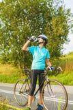 Ritratto piacevole di giovane atleta femminile del ciclista che ha una rottura. Fotografia Stock