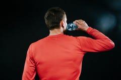 Ritratto posteriore del colpo del pareggiatore caucasico muscolare bello che indossa l'acqua potabile degli abiti sportivi rossi, Immagine Stock