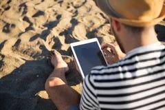 Ritratto posteriore dell'uomo che si siede sulla spiaggia facendo uso della compressa Fotografia Stock Libera da Diritti