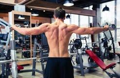Ritratto posteriore di vista dell'allenamento dell'uomo con le teste di legno Fotografia Stock