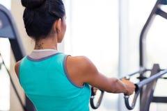 Ritratto posteriore di vista di un allenamento della donna sulla macchina di esercizi Immagine Stock Libera da Diritti
