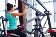 Ritratto posteriore di vista di un allenamento della donna sulla macchina di esercizi Immagini Stock