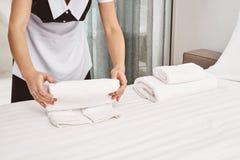 Ritratto potato degli asciugamani di rotolamento del housecleaner sul letto mentre pulendo camera da letto e preparando tutto per fotografie stock libere da diritti