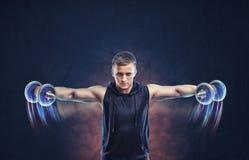 Ritratto potato di un uomo di forma fisica che fa aumento laterale con le teste di legno Immagine Stock
