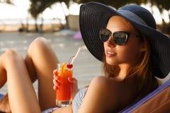 Ritratto ritoccato della giovane donna con il vetro di cocktail che raffredda nel sole tropicale vicino alla piscina su uno sdrai fotografie stock