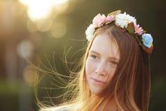 Ritratto rosso della ragazza dei capelli in cerchietto dei fiori sul fondo di verde della natura Immagine Stock