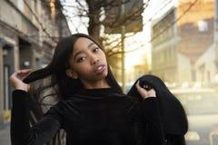 ritratto 20s di giovane donna africana in vestito nero con capelli con il fondo della via della città fotografie stock libere da diritti
