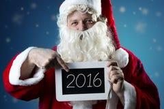 Ritratto Santa Claus che indica sull'ardesia Fotografia Stock