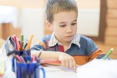 Ritratto schietto di un ragazzo che fa il suo compito e che studia a casa fotografia stock libera da diritti