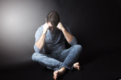 Ritratto scuro dell'uomo che si siede nello scuro e Immagini Stock