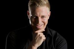 Ritratto scuro dell'uomo seducente sorridente che guarda diritto. Immagini Stock