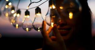 Ritratto sensibile di giovane donna attraente con il bello sorriso che tocca le lampadine sulla corda durante il tramonto archivi video