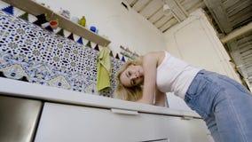 Ritratto sexy di giovane donna bionda in cucina moderna azione Bionda sexy negli sguardi della cucina alla condizione della macch video d archivio