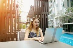 Ritratto soleggiato della ragazza con il fiore ed il computer portatile vicino allo stagno Fotografie Stock Libere da Diritti