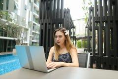 Ritratto soleggiato della ragazza con il fiore ed il computer portatile vicino allo stagno Immagini Stock