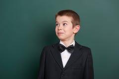 Ritratto sorpreso del ragazzo di scuola vicino al fondo in bianco verde della lavagna, vestito in vestito nero classico, un allie Fotografia Stock Libera da Diritti