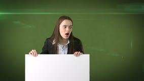 Ritratto sorpreso della donna di affari con il bordo bianco in bianco su verde Modello femminile con capelli lunghi Immagine Stock