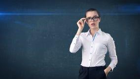 Ritratto sorpreso della donna di affari in gonna bianca su fondo isolato con il divieto dei capelli ed i vetri arancio e neri Immagine Stock Libera da Diritti